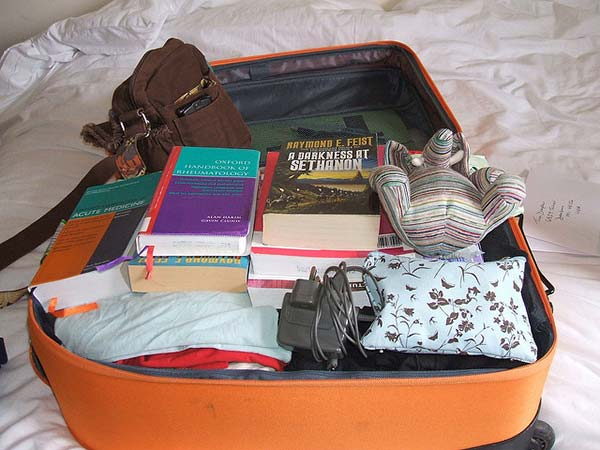 Open suitcase with clothing and books