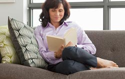 Mid age woman sitting on the sofa reading a book