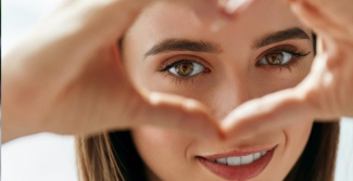 Girl with hands in a heart shape over her eyes