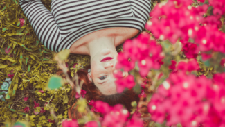 woman laying under pretty pink flowers