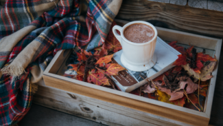 Autumn scene with a cup of hot chocolate, a book and a blanket