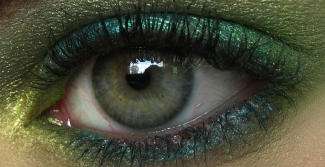 Green eye shimmery makeup close up